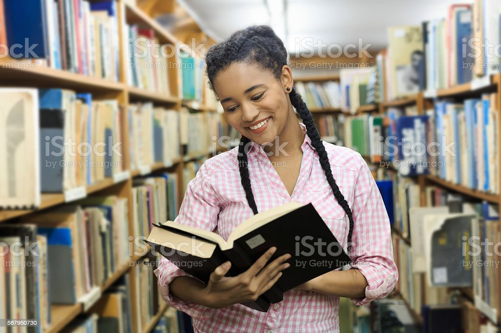 Smiling female student reading a book in the library stock photo