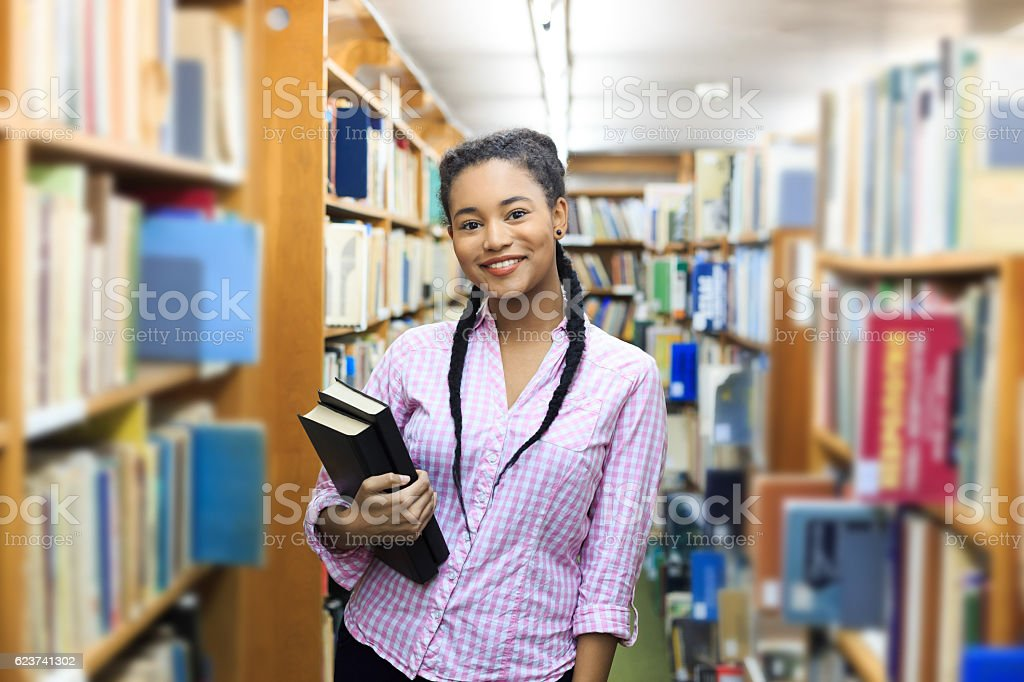 Smiling female student standing at the library stock photo