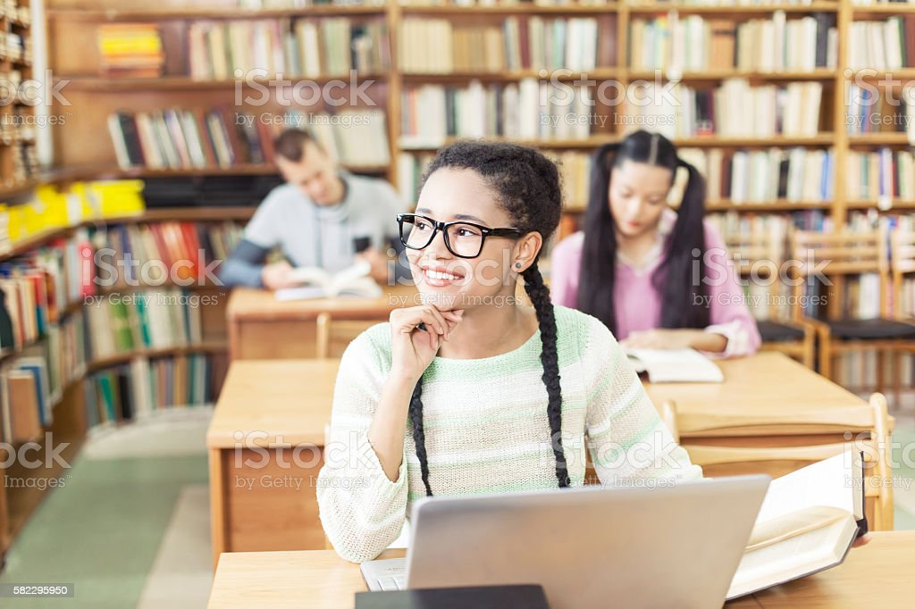 Smiling female student using laptop at library stock photo