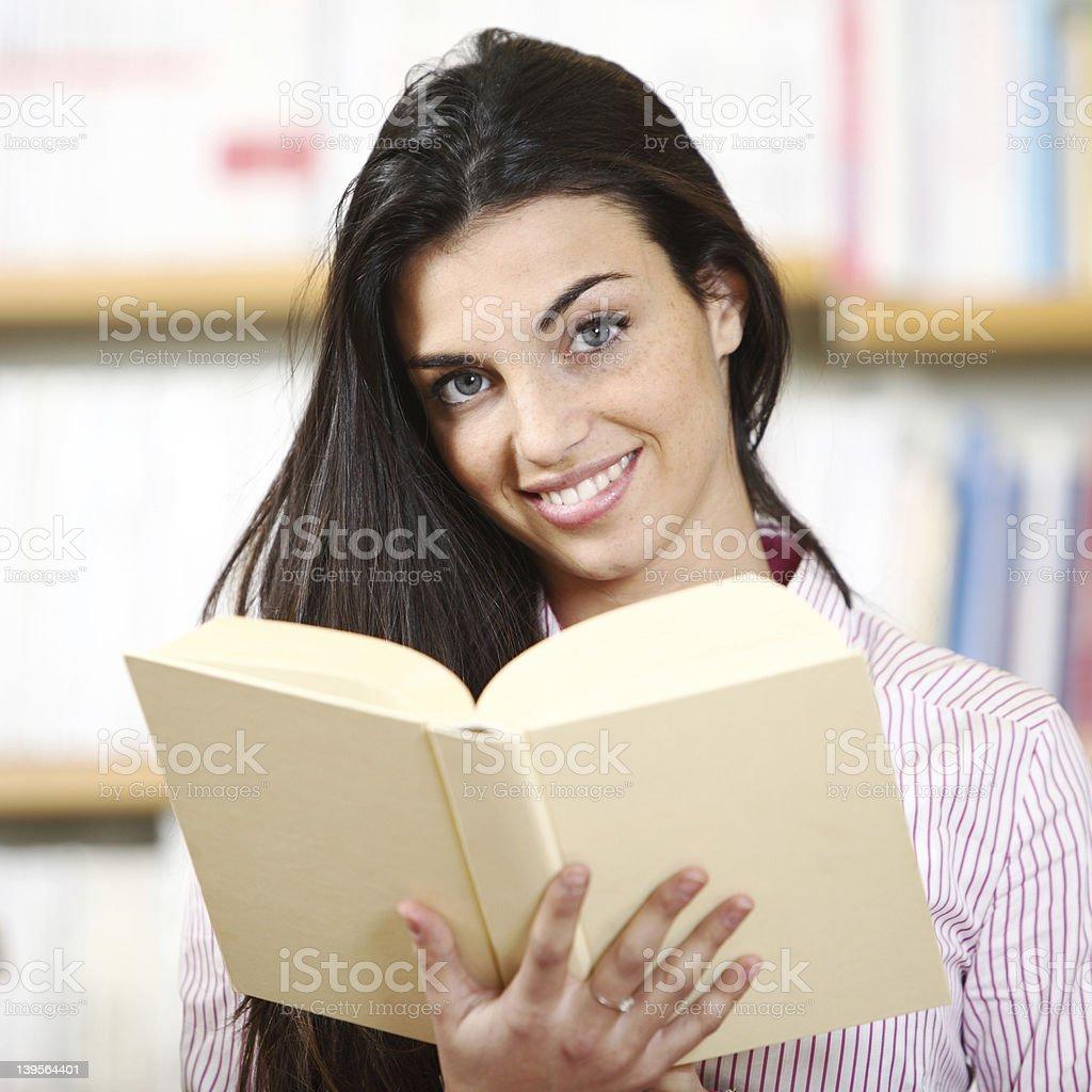 Souriante étudiante avec un livre photo libre de droits