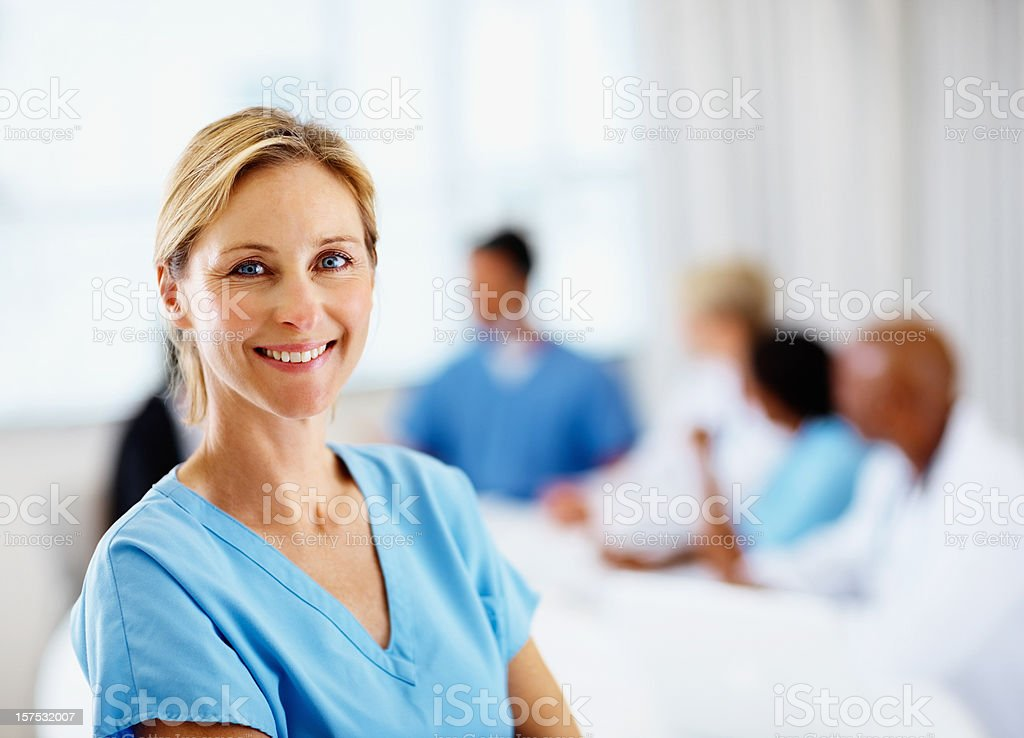 A smiling female surgeon with colleagues at a table behind royalty-free stock photo