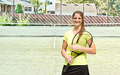 Smiling female tennis player in field