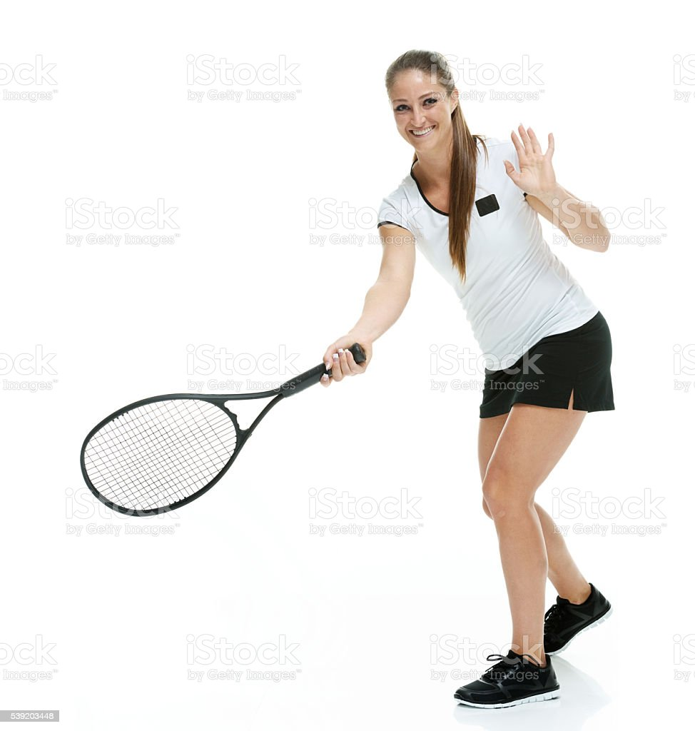 Smiling female tennis player swinging stock photo