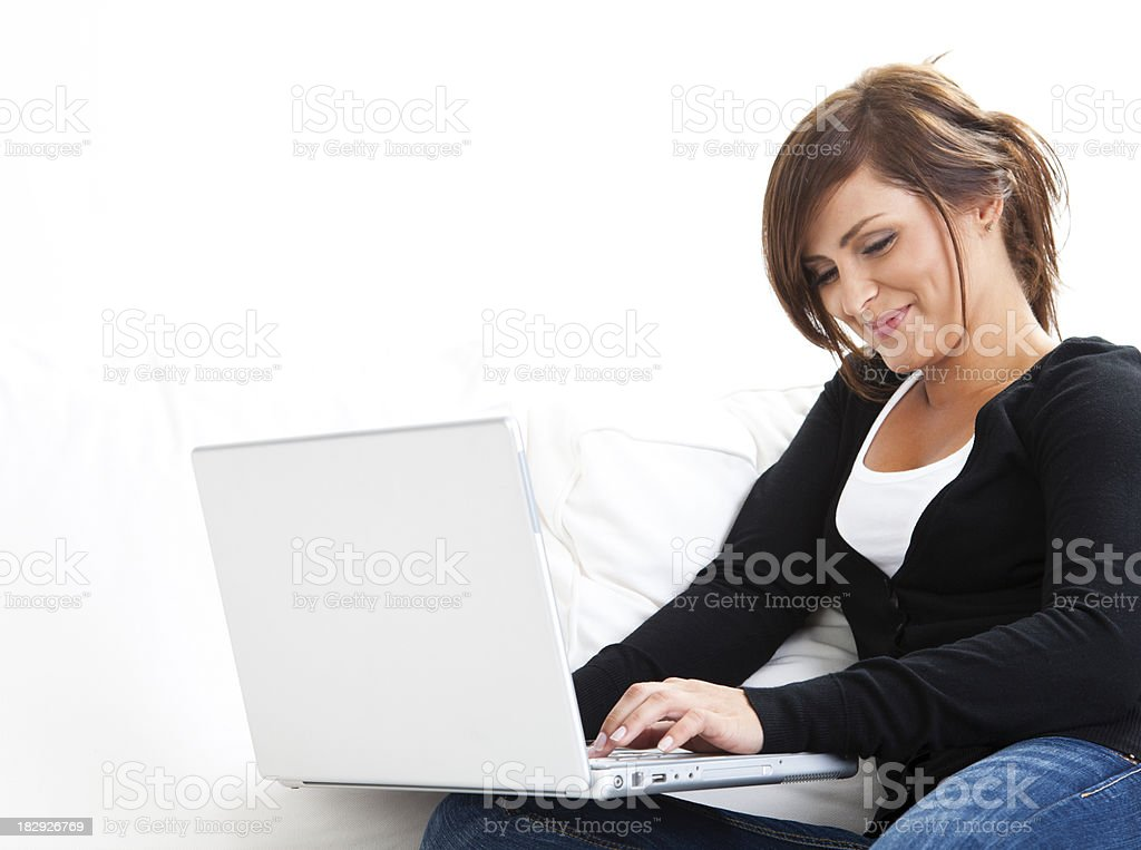 Smiling female using laptop at home royalty-free stock photo