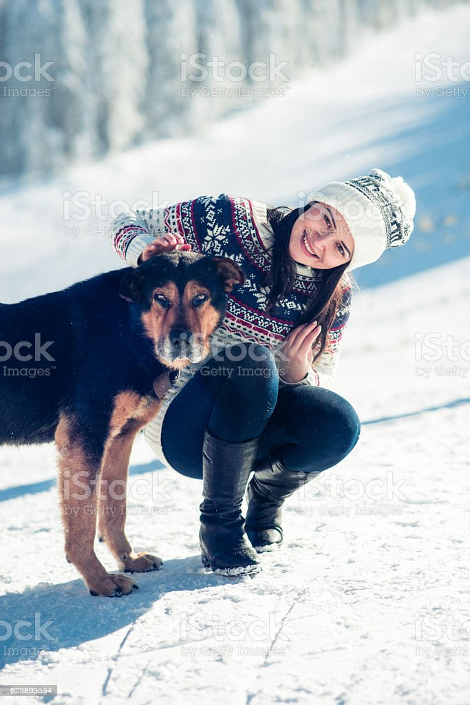 Smiling Female with Her Dog at Snowy Mountains stock photo