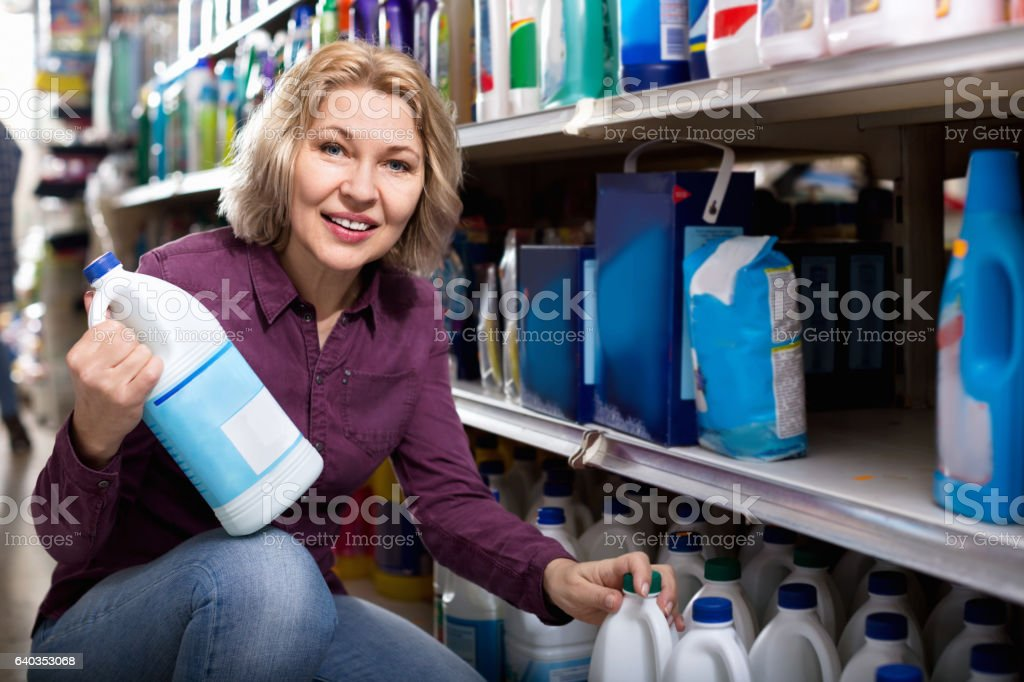 Smiling female with selecting fabric conditioner stock photo