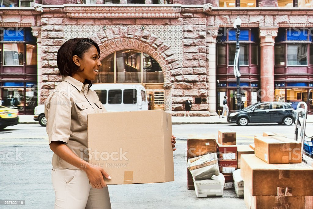 Smiling female worker carrying box outdoors stock photo