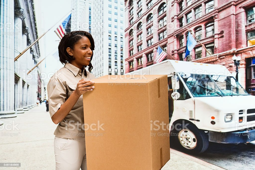 Smiling female worker holding box outdoors stock photo