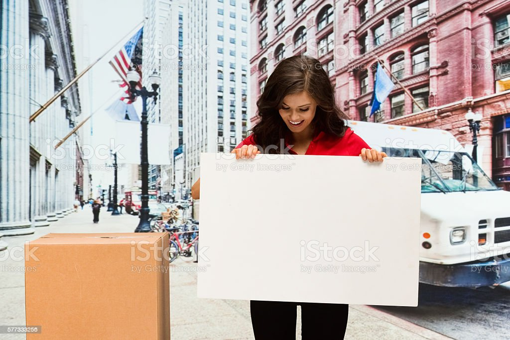 Smiling female worker holding placard outdoors stock photo