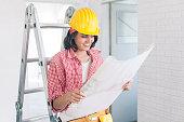 Smiling female worker looking at work plan