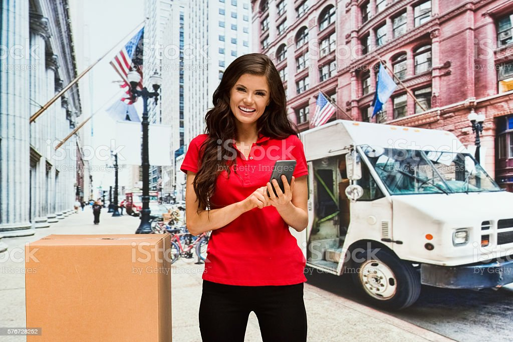Smiling female worker using phone outdoors stock photo