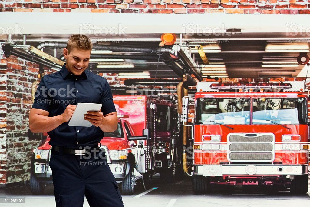 Smiling fire fighter using tablet in fire station stock photo