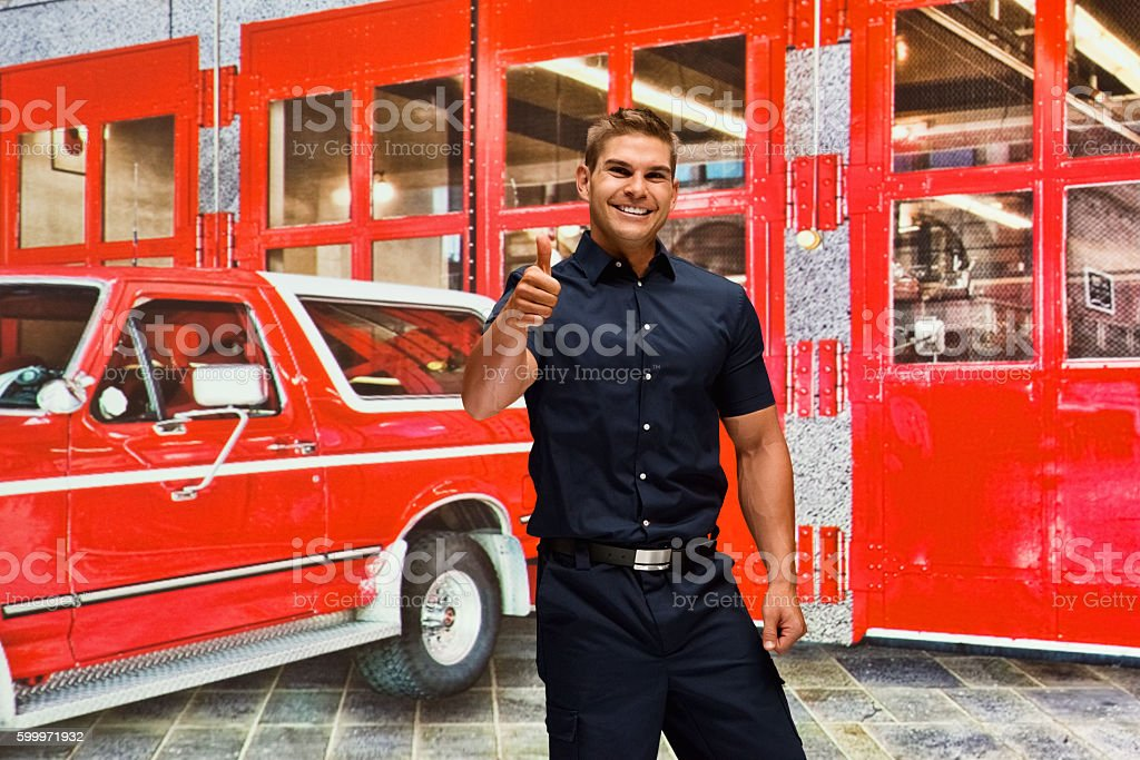 Smiling fireman giving thumbs up stock photo