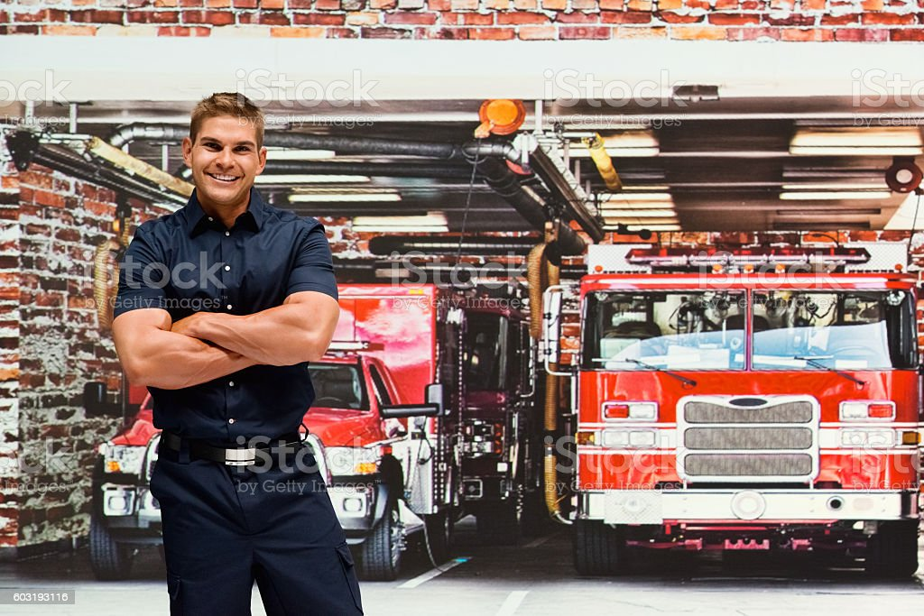 Smiling fireman in fire station stock photo