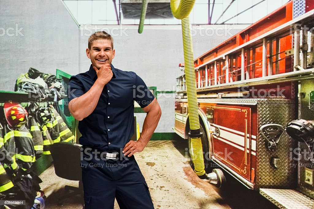 Smiling fireman standing in fire station stock photo