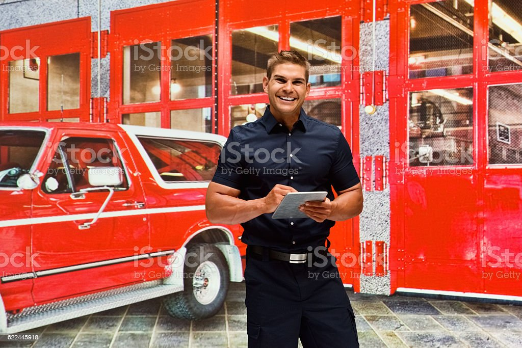 Smiling fireman using tablet in fire station stock photo
