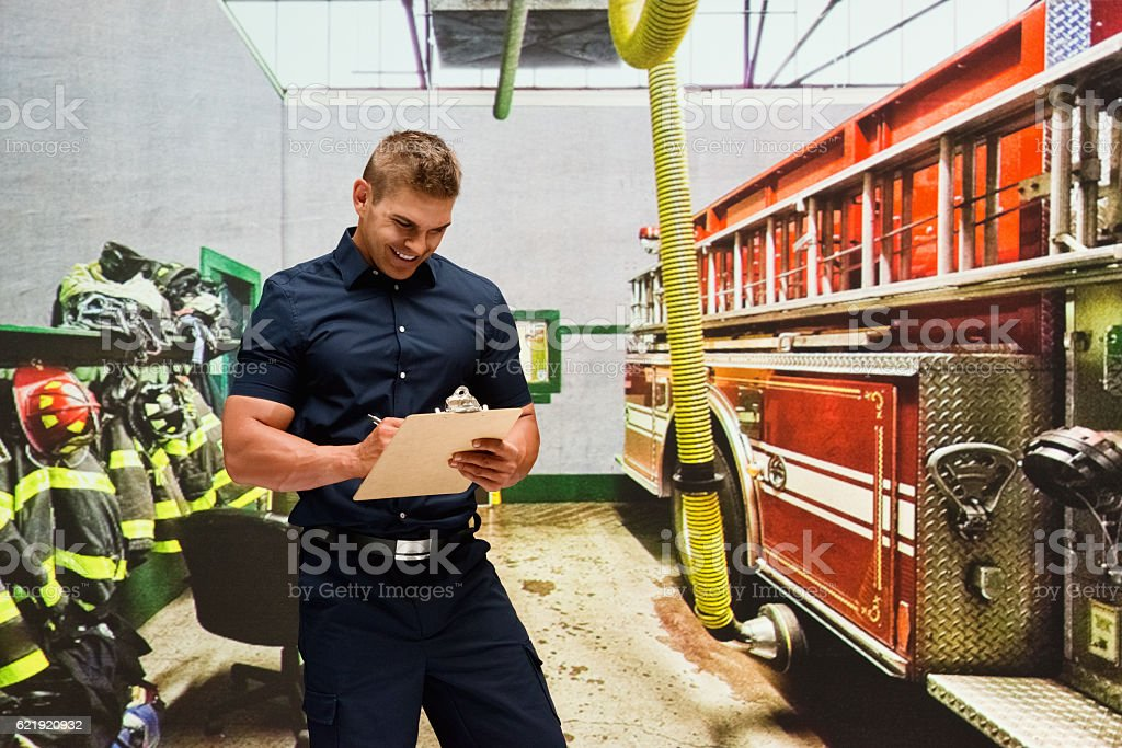 Smiling fireman working in fire station stock photo