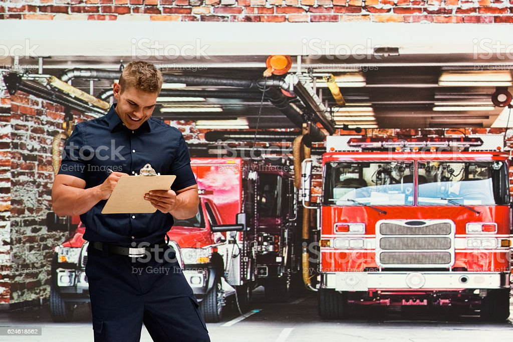 Smiling fireman writing on clipboard in fire station stock photo