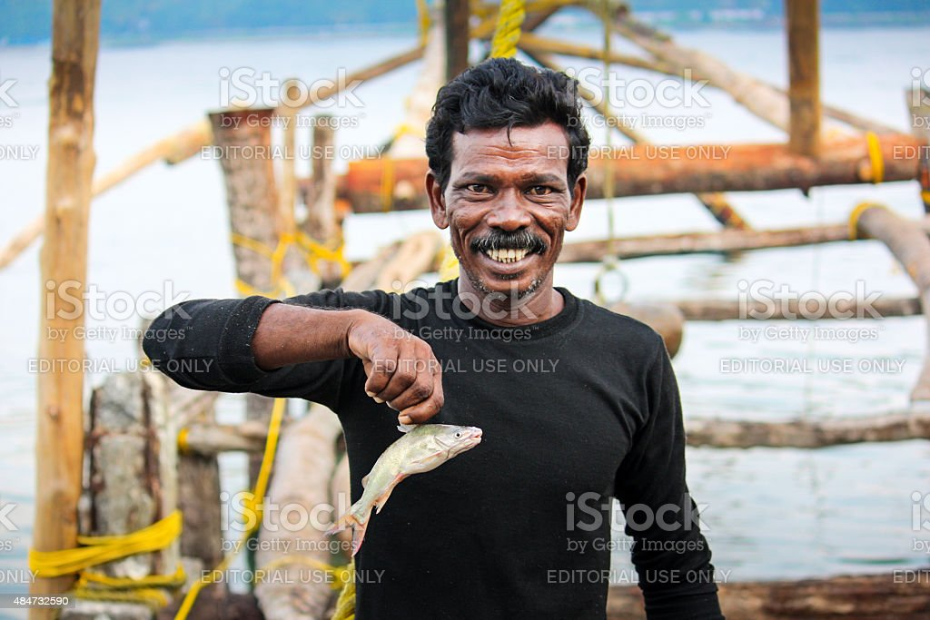 Smiling Fisherman Fishing at Fort Kochi Kerala India stock photo