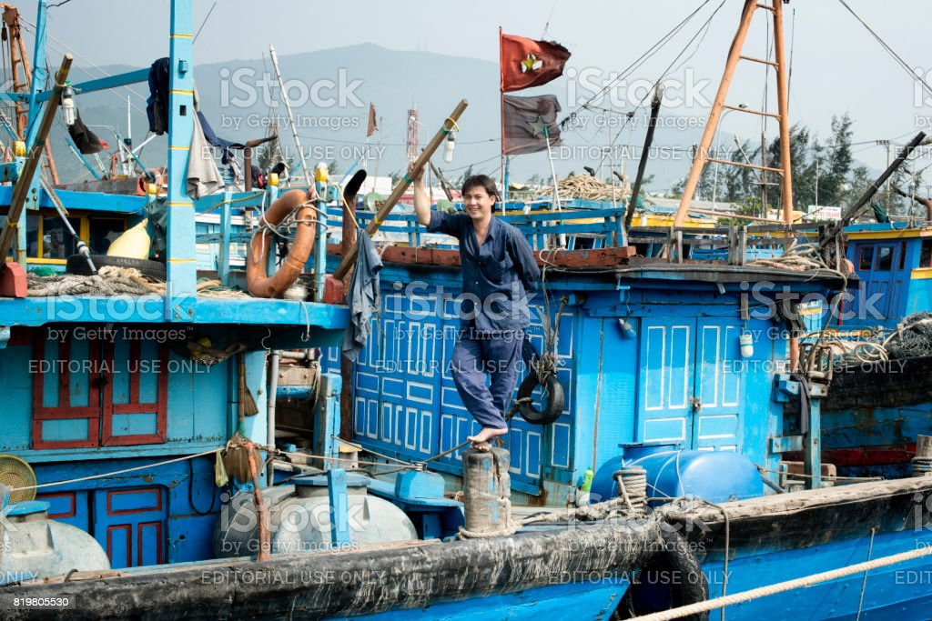 Smiling fisherman standing on his boat. December 26, 2013 - Da Nang, Vietnam stock photo