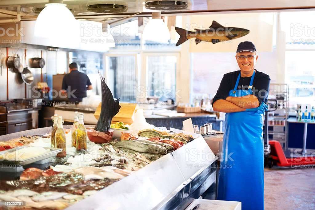 Smiling fishmonger in store stock photo