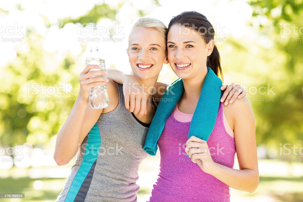 Smiling Fit Friends Standing Arms Around In Park stock photo
