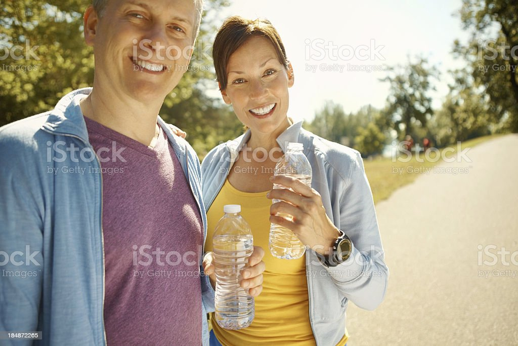 Smiling fitness couple holding water bottle royalty-free stock photo