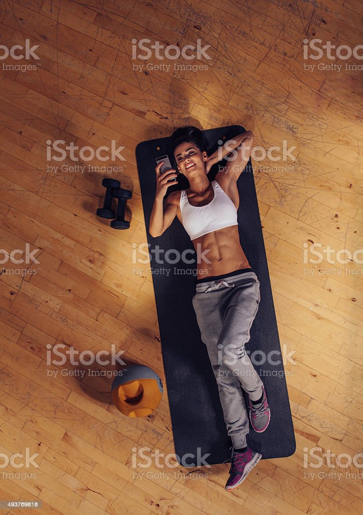 Smiling fitness female using mobile in gym stock photo
