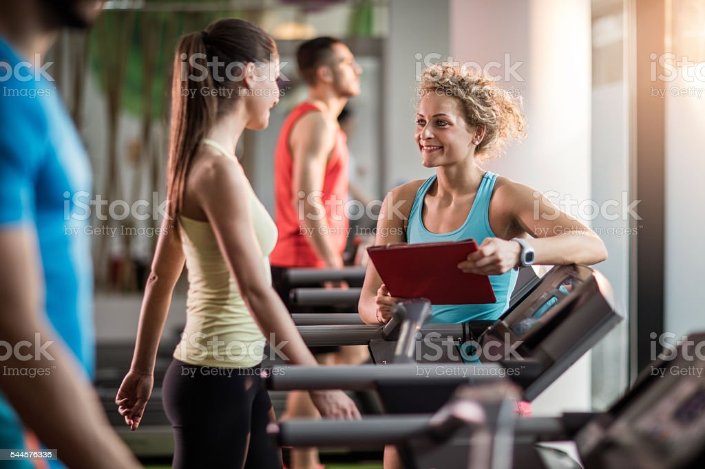 Smiling fitness trainer talking to young woman in a gym. stock photo
