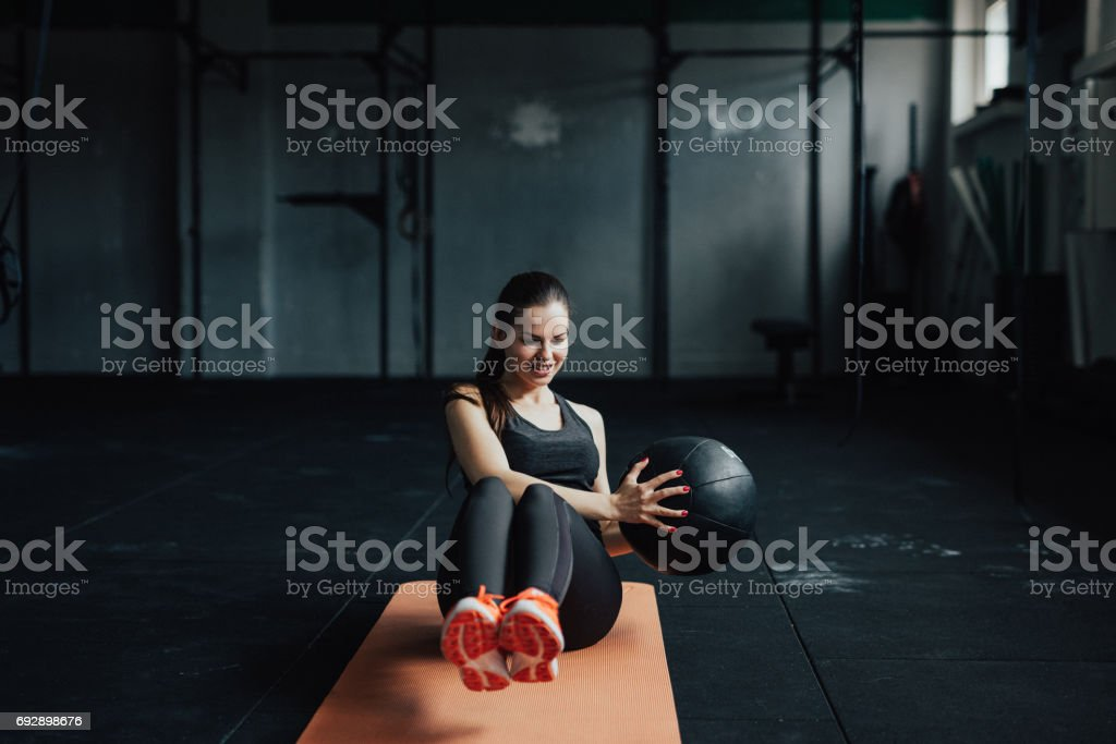 Smiling fitness woman doing exercises with the medicine ball on the...
