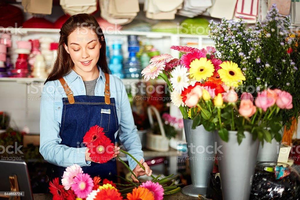 Smiling florist arranging fresh Gerbera daisies in flower shop stock photo