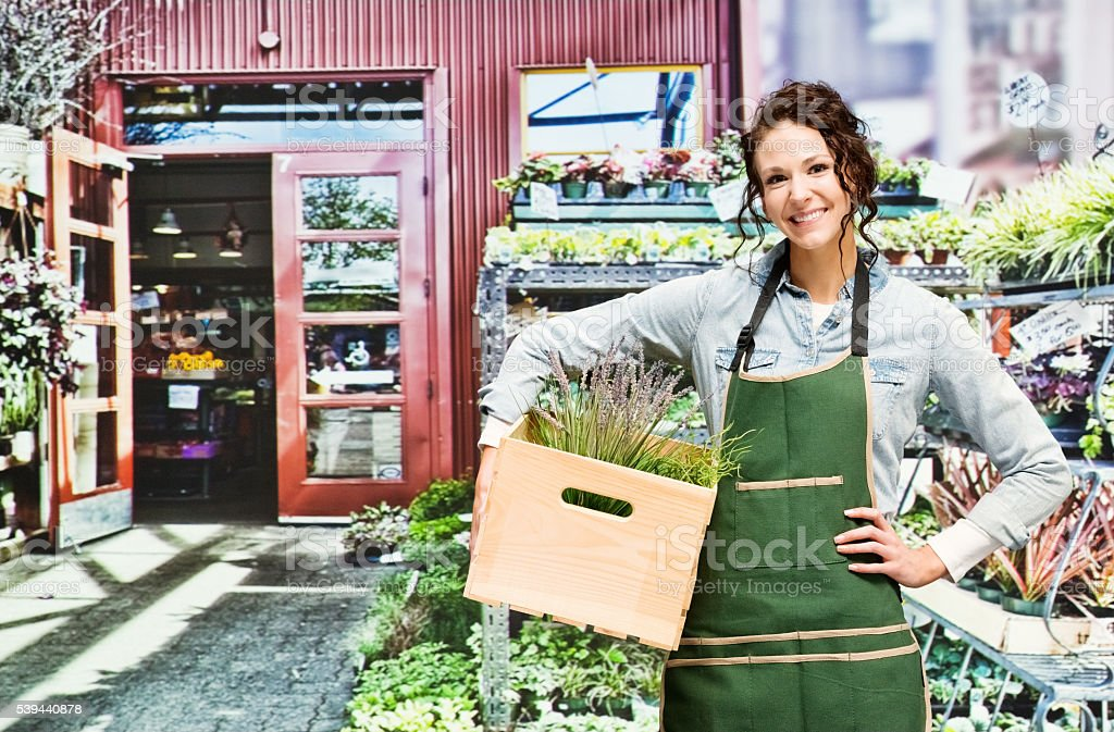 Smiling florist holding box in flower shop stock photo