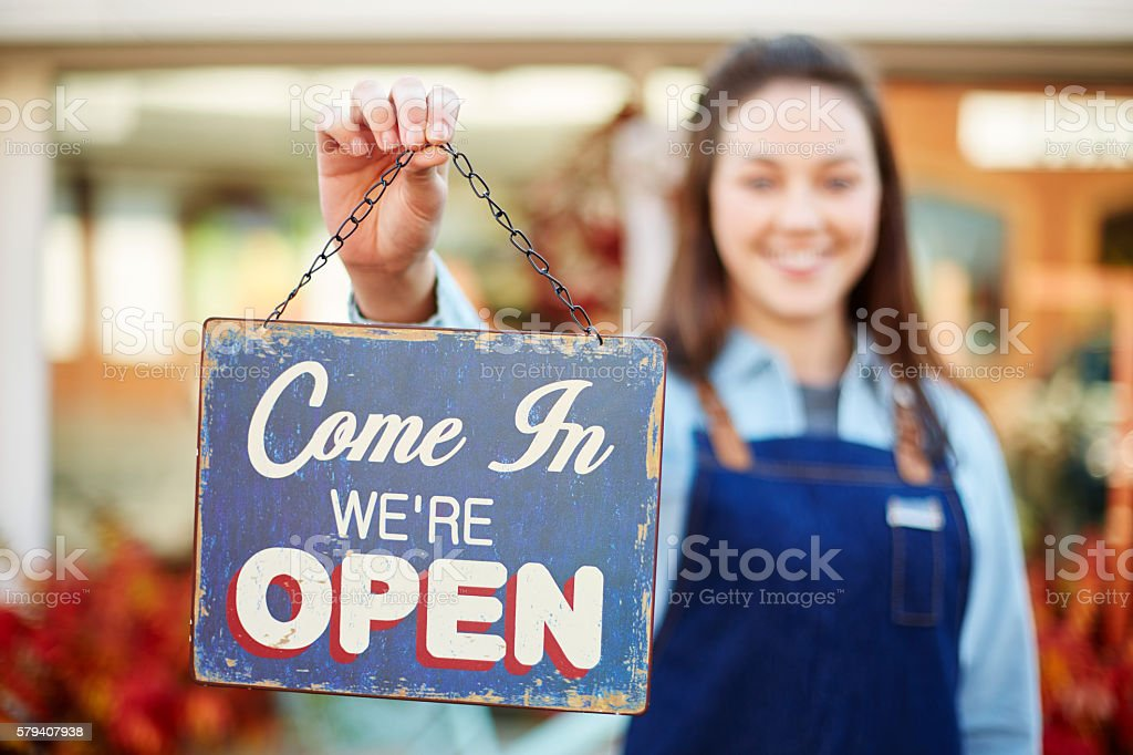 Smiling florist holding up sign saying come in we're open stock photo
