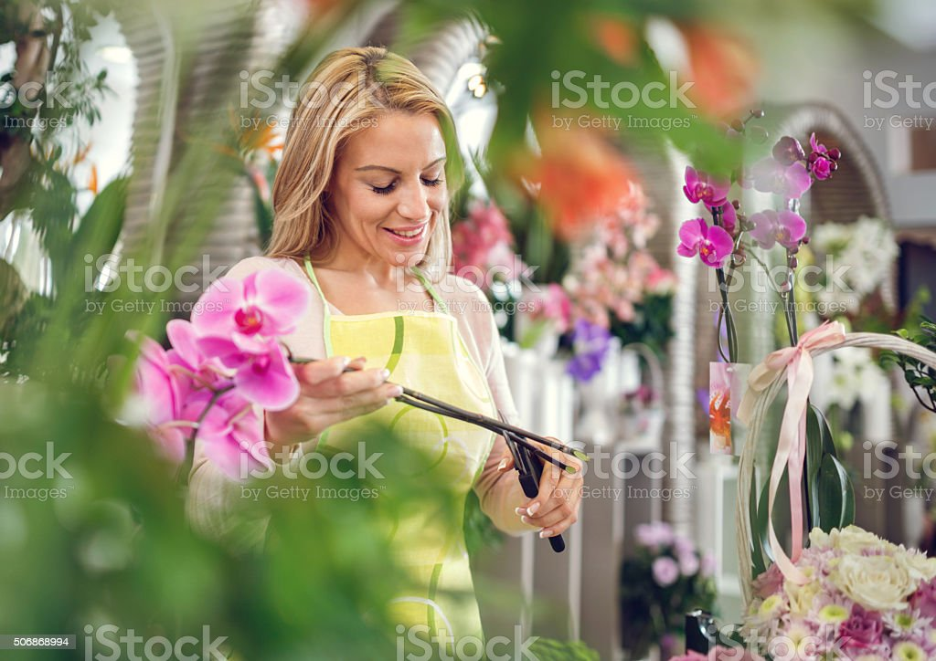Smiling florist making bouquet of orchids in flower shop. stock photo