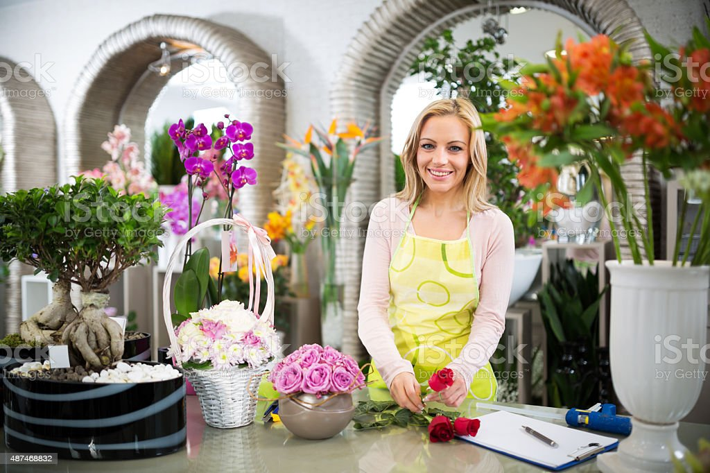 Smiling florist making bouquet of roses and looking at camera. stock photo