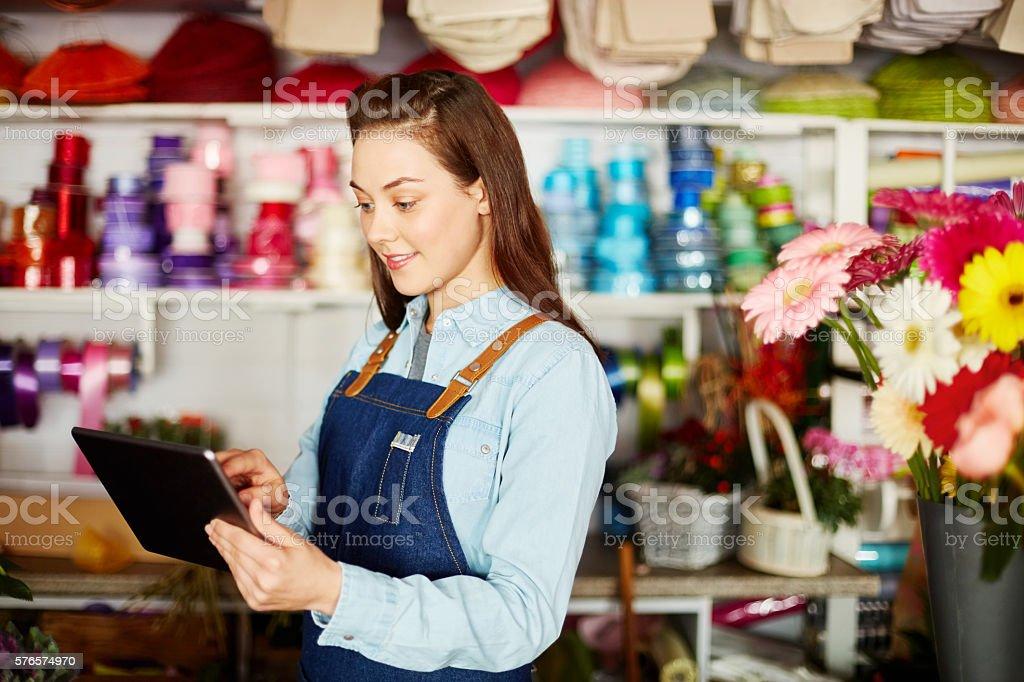 Smiling florist using digital tablet in flower shop stock photo