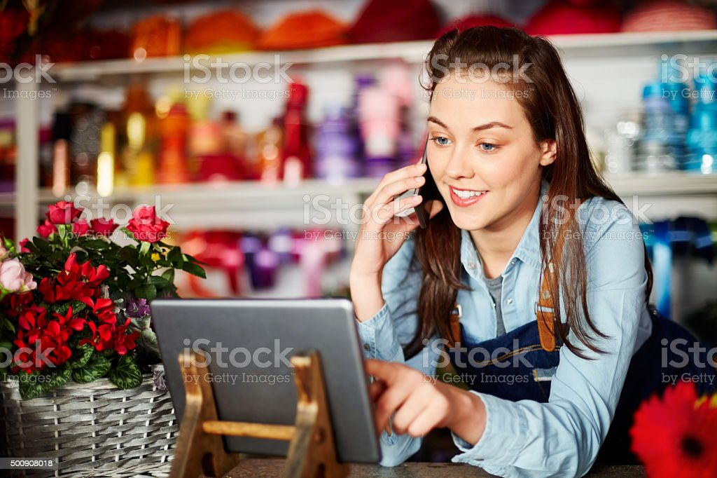 Smiling florist using technologies at flower shop stock photo