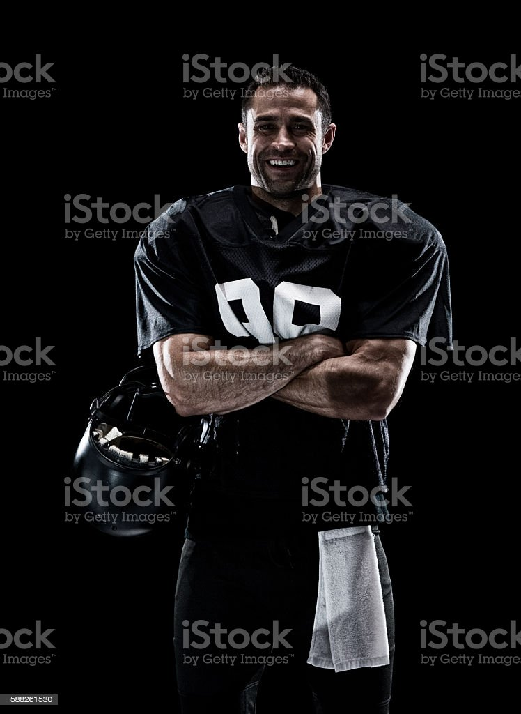 Smiling football player standing stock photo