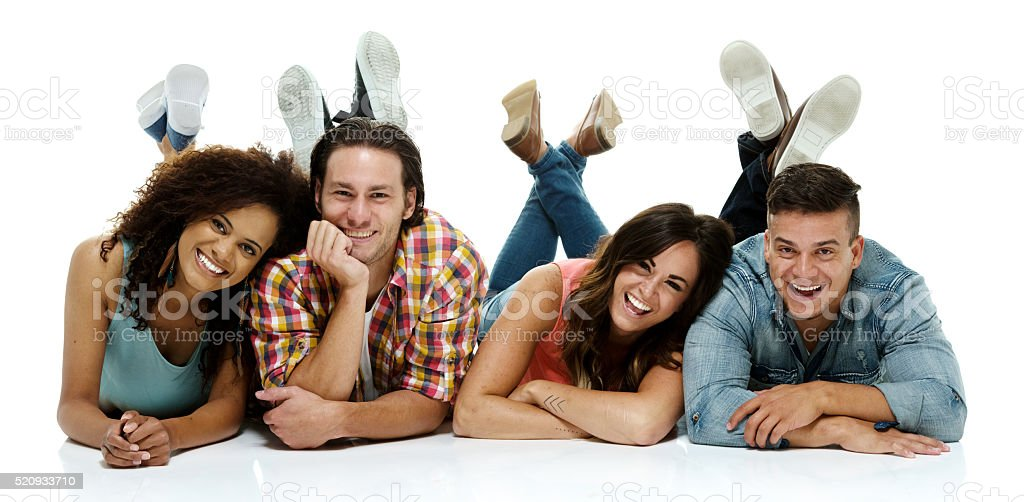 Smiling four friends lying on floor stock photo