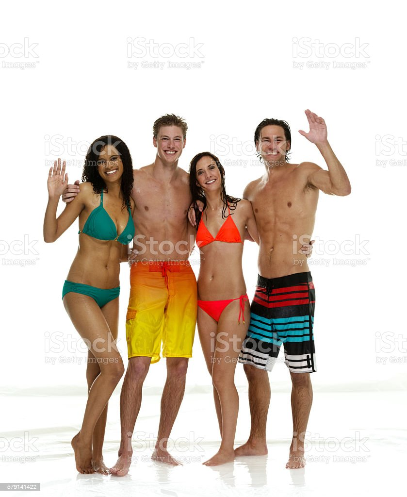 Smiling four friends standing and waving hand stock photo