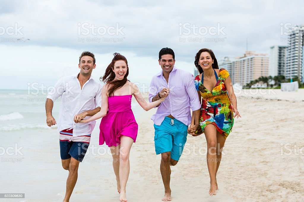 Smiling four people holding hands and running on the beach stock photo