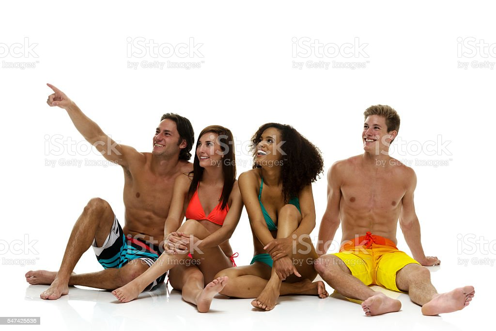 Smiling four swimmer sitting and pointing stock photo