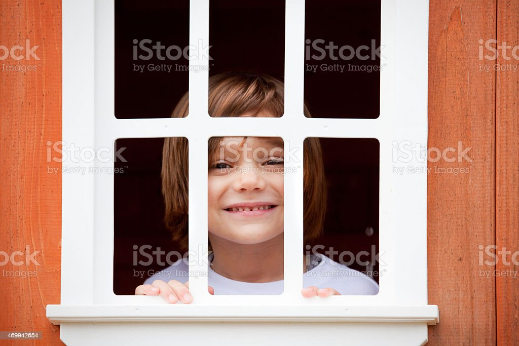 Smiling Four Year Old Boy Peeking Though Window stock photo