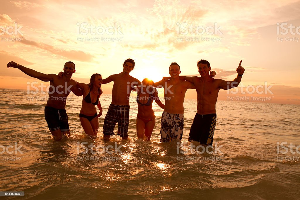 Smiling friends at beach in golden silhouette under the sun royalty-free stock photo