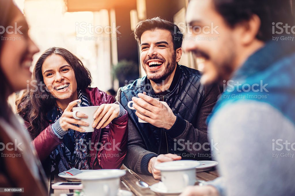 Smiling friends drinking coffee stock photo