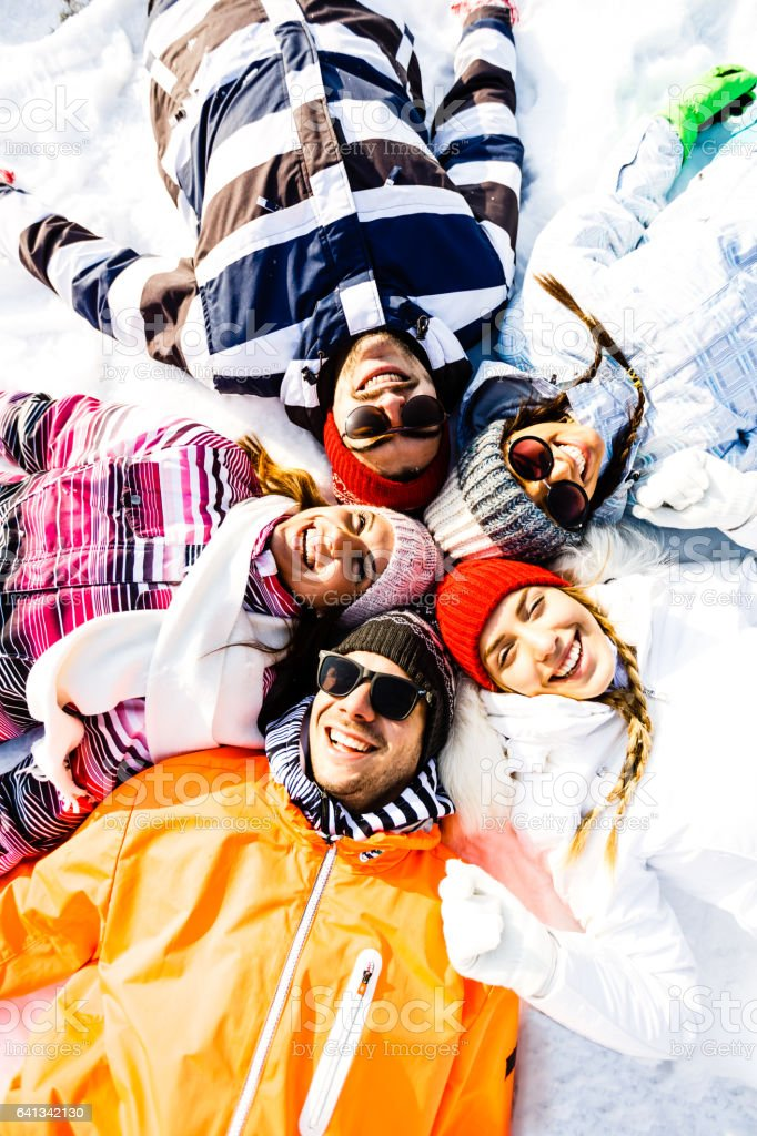 Smiling friends laying in snow in circle stock photo