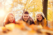 Smiling friends lying down in autumn park.