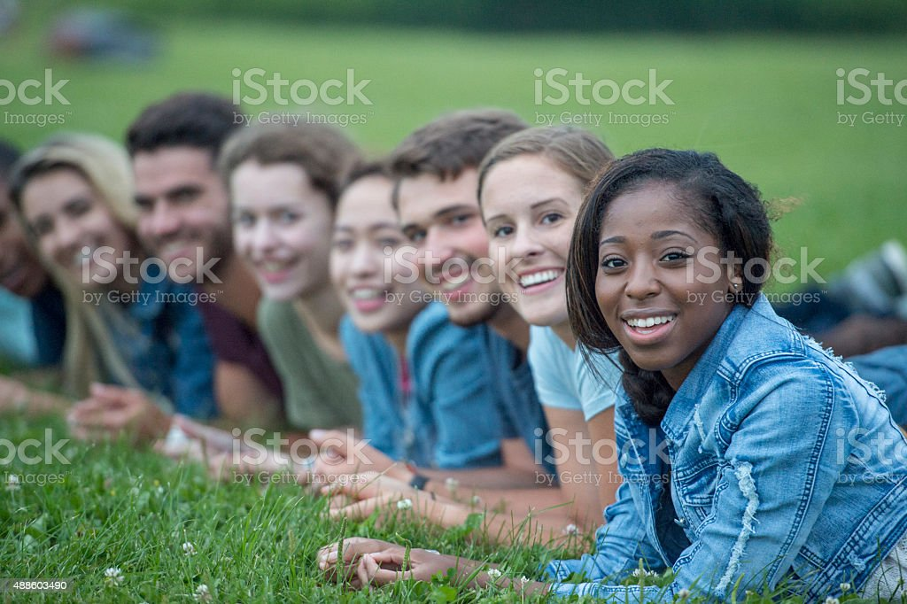 Smiling Friends Lying in a Row stock photo