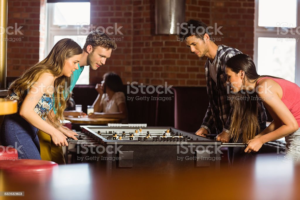 Smiling friends playing table football stock photo