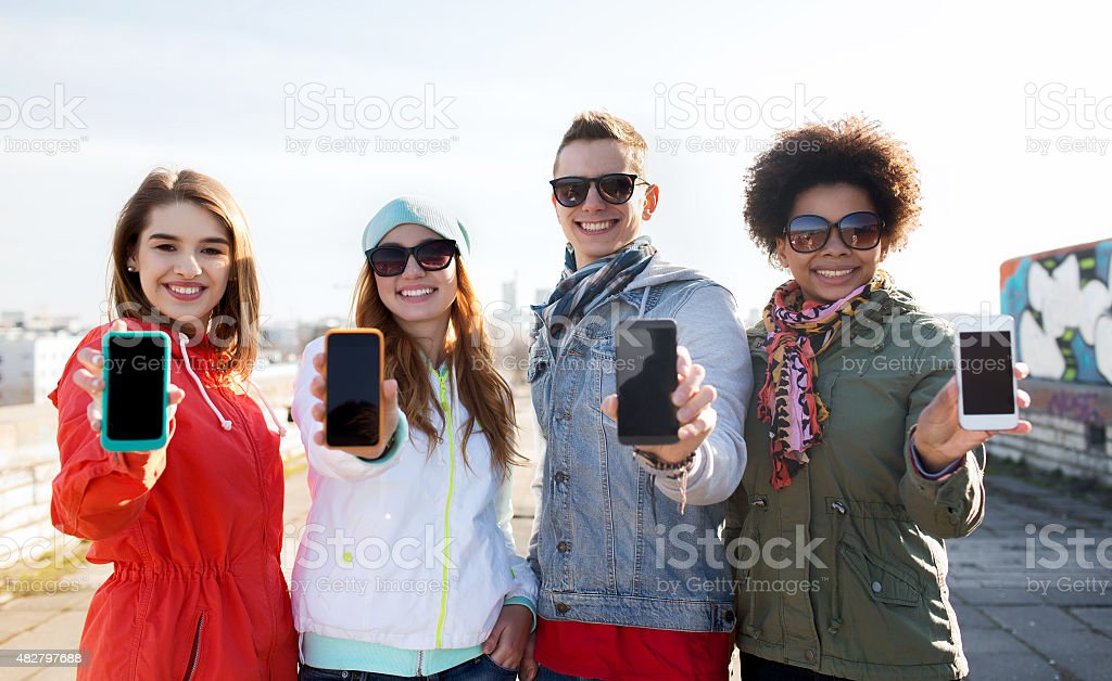 smiling friends showing blank smartphone screens stock photo